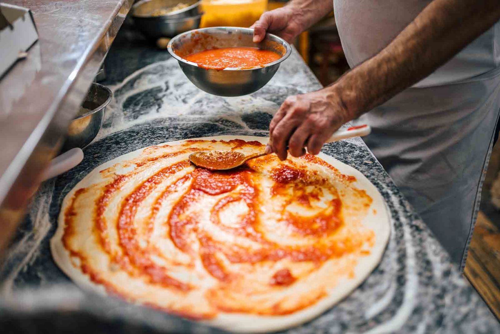Chef spreading sauce on a pizza crust