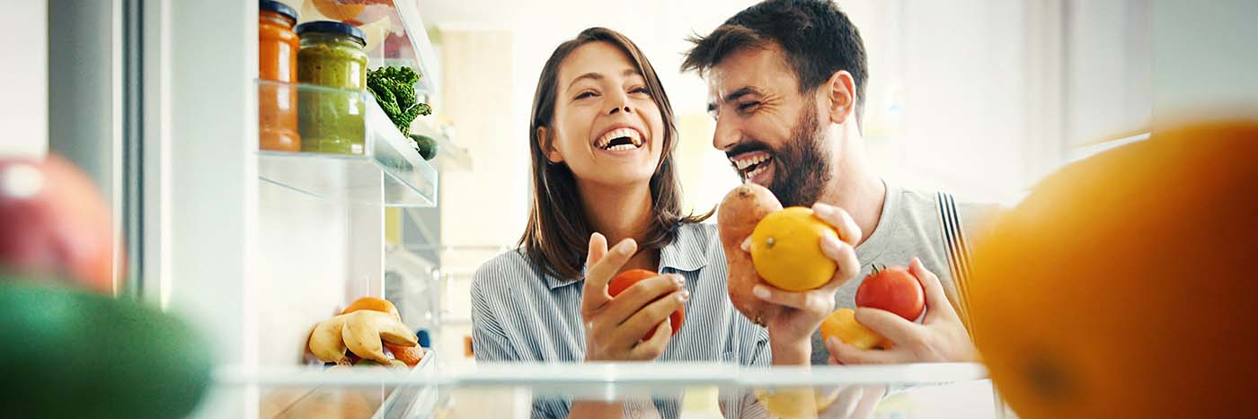 Couple opening their fridge and smiling because it's stocked with food
