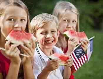 Kids eating watermelon and holding small American flags