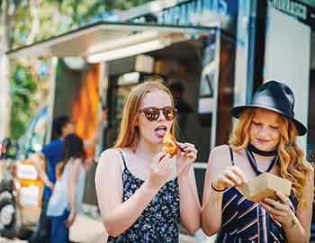 Teenage girls eating food from a food truck