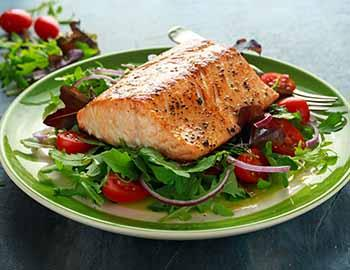 Grilled salmon on a plate of greens