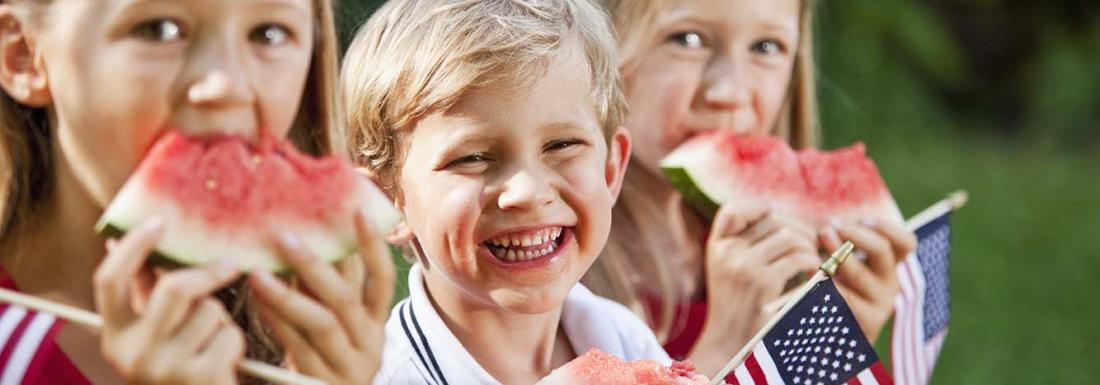 Kids eating watermelon holding small American flags