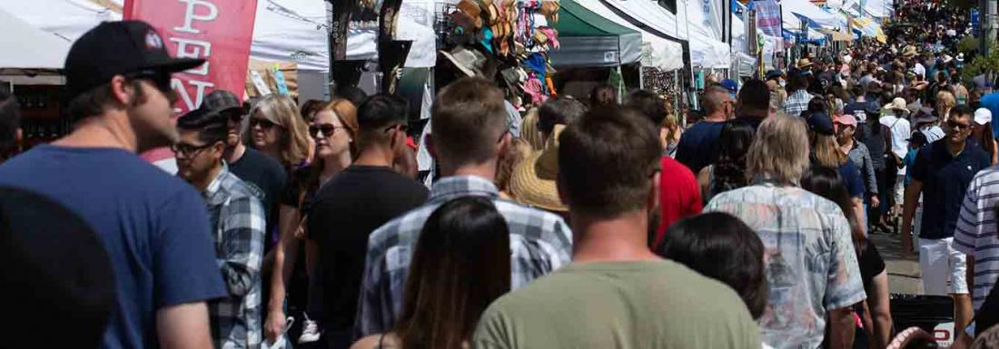 Attendees walking by shops at an outdoor community event