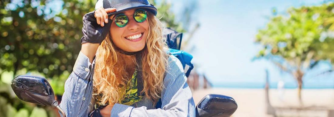Woman riding motorcycle near the beach smiling