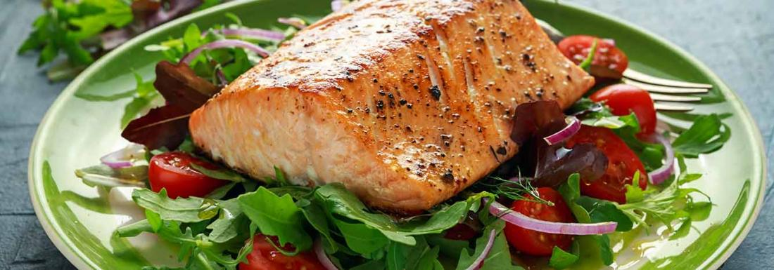 Grilled salmon on a plate of fresh salad greens