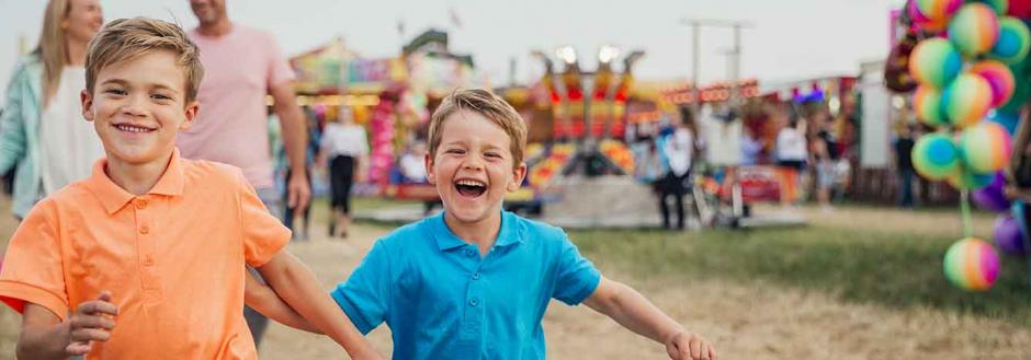Two young boys running and smiling while attending a state fair