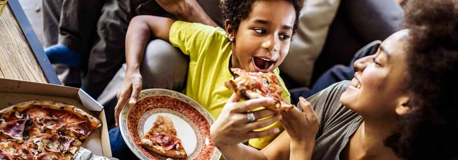 Mother and son enjoying pizza together