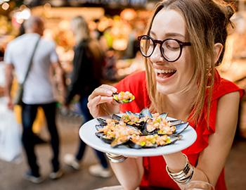 Woman eating mussels at a seafood restaurant