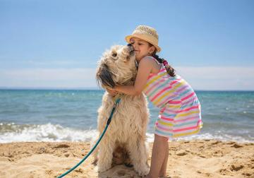 girl hugging her dog on the beach at the Grand Strand
