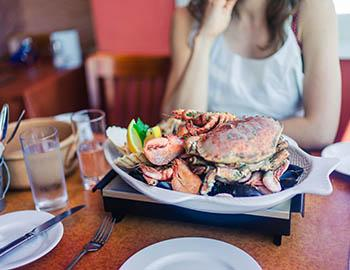 Woman sitting at table in front of a big plate of seafood