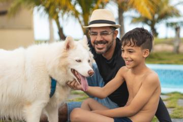 Father and son petting their dog on vacation