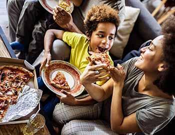 Mom feeding her son a slice of pizza
